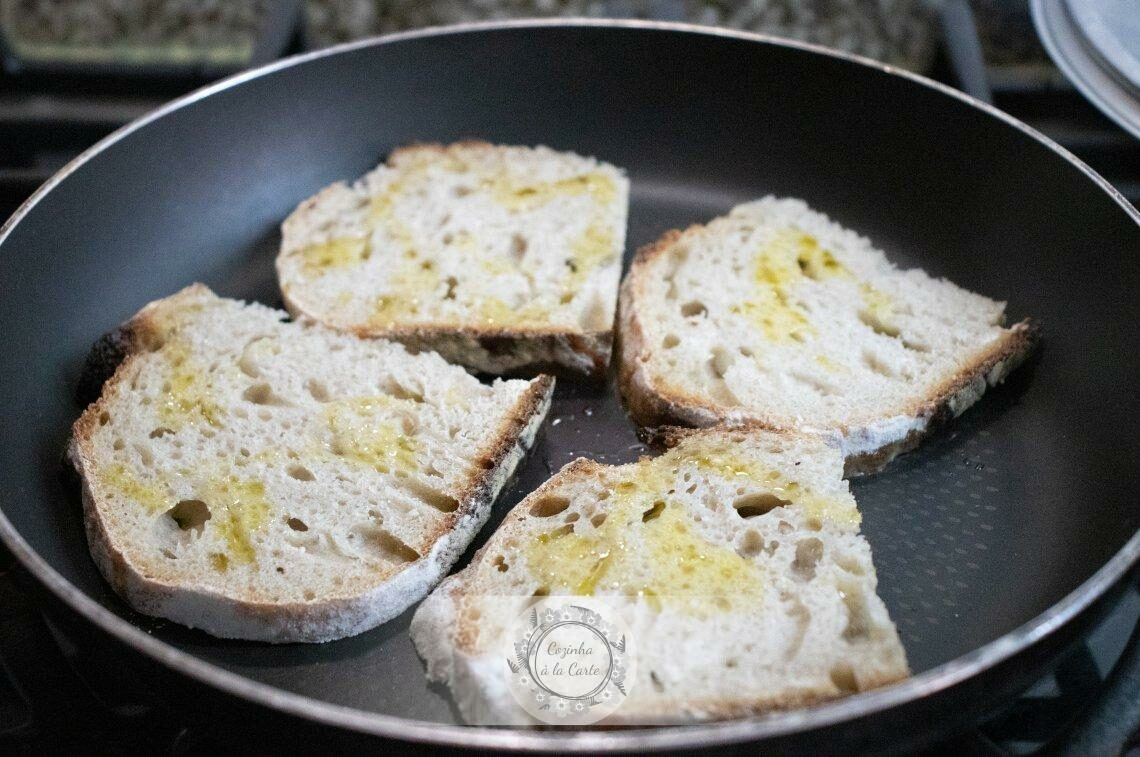 Barre cada fatia de pão com azeite e leve-as a torrar numa frigideira, sobre o lume