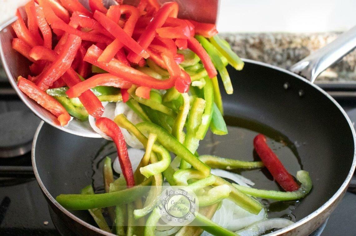 Quando o azeite aquecer, junte os pimentos e a cebola à frigideira